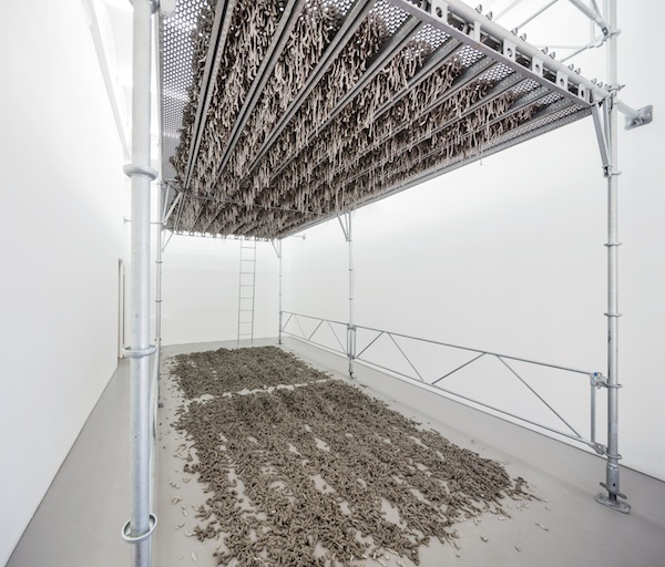 Kristina Matousch, Still Life Production, 2013, scaffolding, steel planks, clay, 3 x 6 x 4 m. During the performance on April 4th, the artist trampled trampled two tonnes of clay through the holes of the platform.