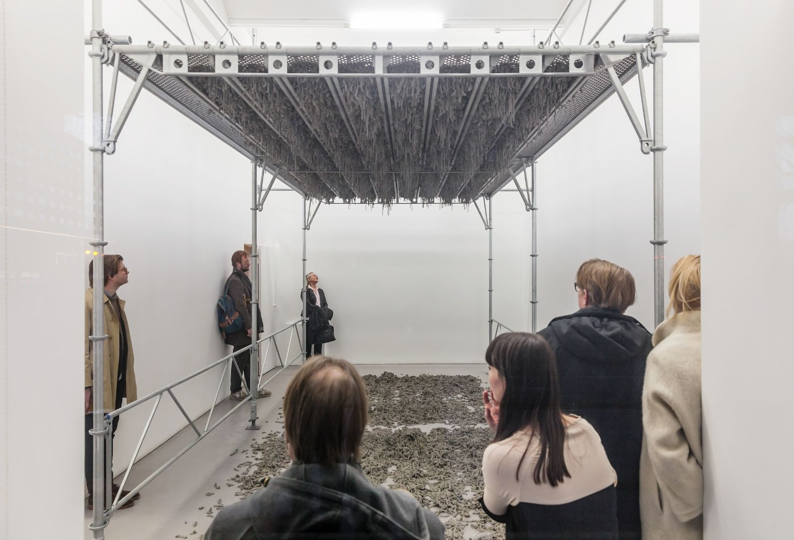 Still Life Production, 2013, scaffolding, steel planks, clay, 3 x 6 x 4 m. During the performance in Galleri Riis, Stockholm, 2013, the artist trampled three tons of clay through the holes of the platform.