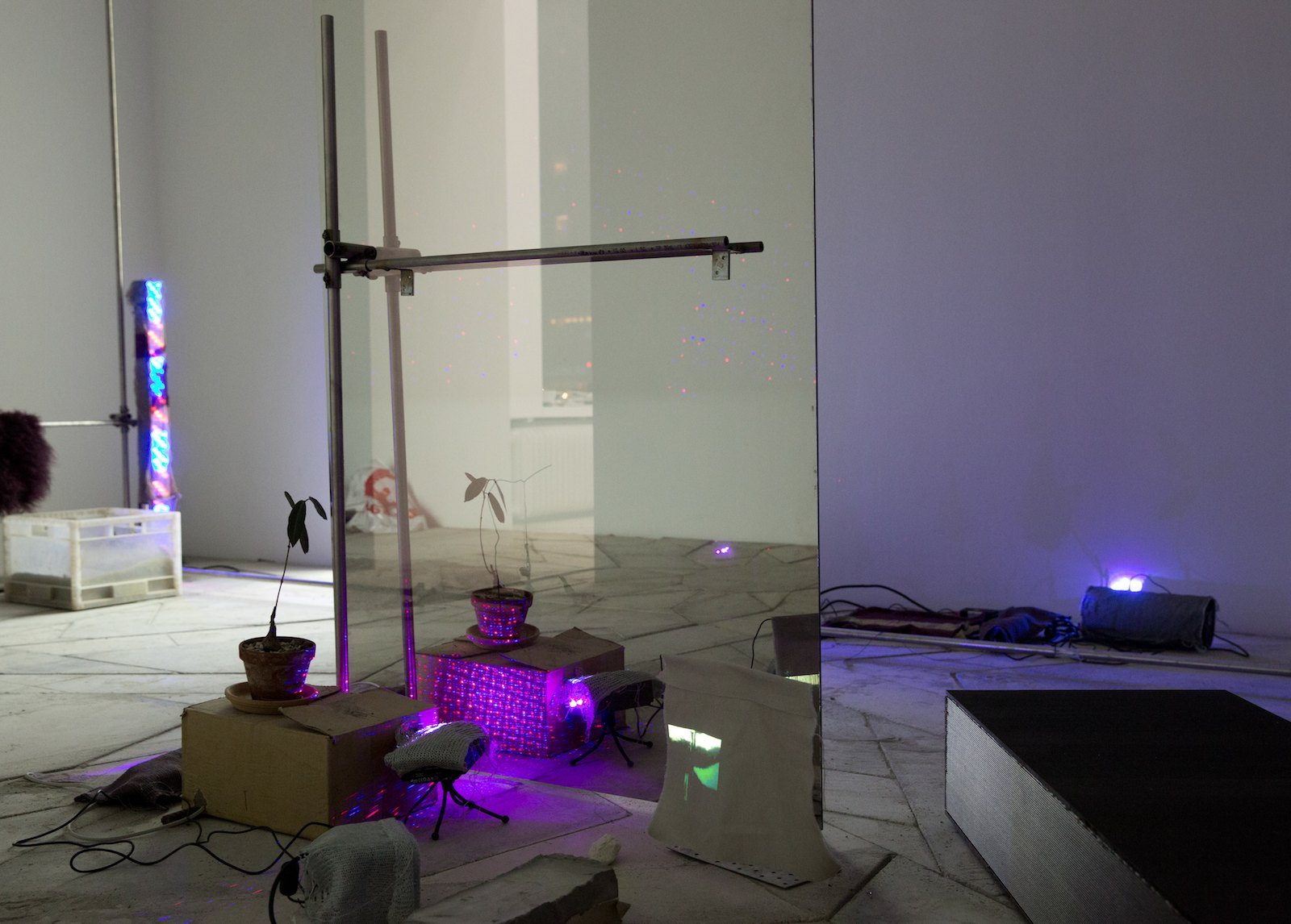 Endless promises, 2014, steel pipes, coloured lambskin, knitting, PC, projector, speakers, concrete, cardboard, ceramics, black marbrite glass, heating element, semi-transparent-mirror, shell, cigarette butt, LED-light, laser loop, video loop, crocheting, Petopentia Natalensis plants, plastic pearls, ruby in fuchsit. Dim. variable